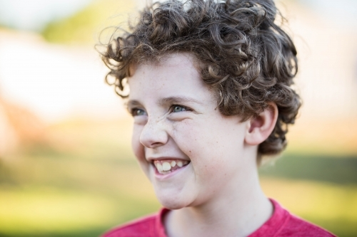 Young boy with curly hair laughing looking away