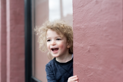 Young boy with curly hair laughing outside a pink building
