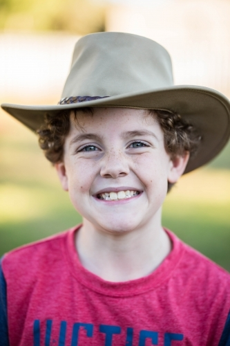 Young boy with curly hair wearing akubra hat smiling