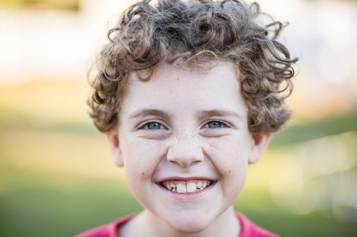 Young boy with curly hair with big smile