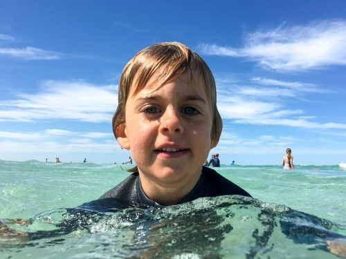 Young boy with head above water in ocean looking at camera