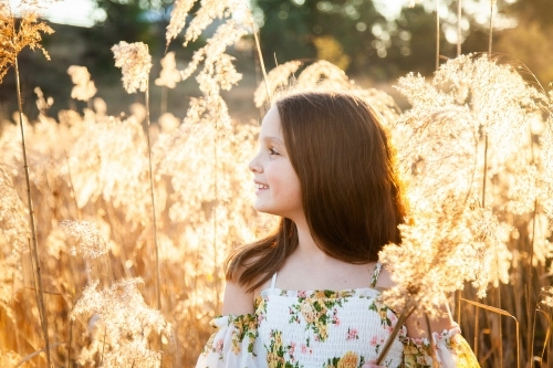 Young brunette girl looking off into the distance backlit by golden light
