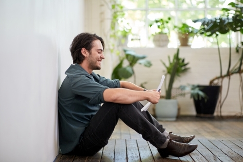 Young business man relaxing sitting on a timber floor in studio