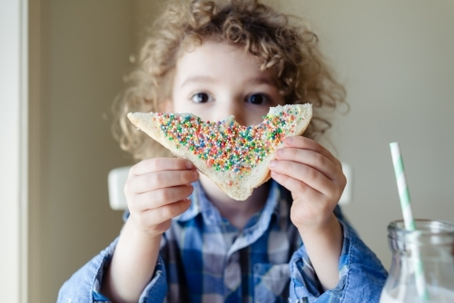 Young child with curly hair holding up a slice of fairy bread