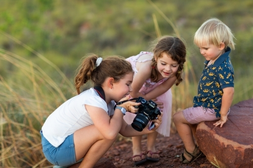 young children looking at photo on back of camera