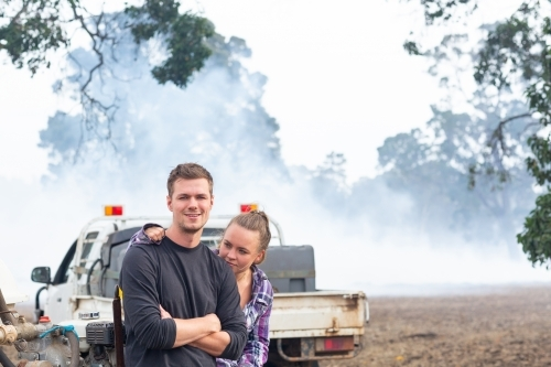 Young couple in front of ute with smoke in background