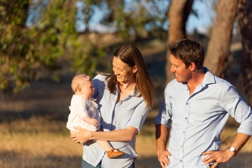Young couple outdoors with their baby girl in the sunshine