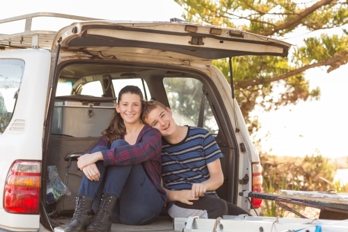 Young couple sitting on back of 4WD