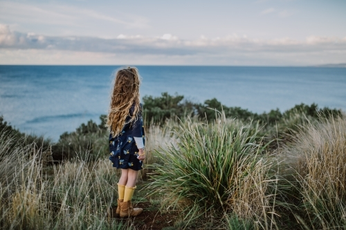 Young fashionable girl standing on a cliff top looking out to the ocean