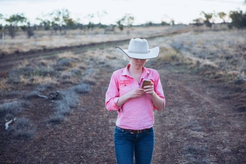 Young female farmer using smart phone in paddock