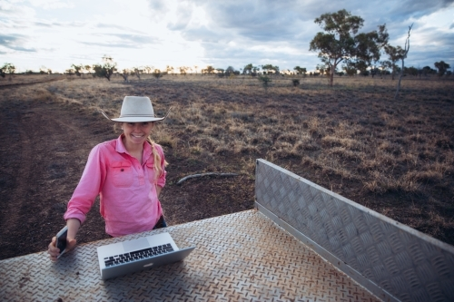 Young female farmer with communication devices
