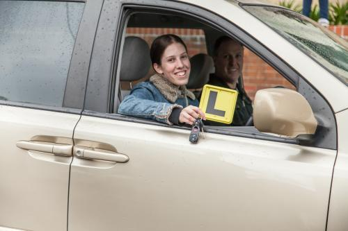 Young female learner driver being supervised by her father