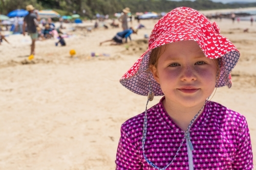 Young girl at the beach wearing a hat and rashie