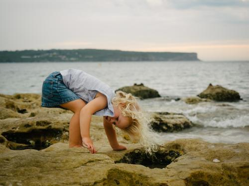 Young girl bending to look in rockpools at the beach