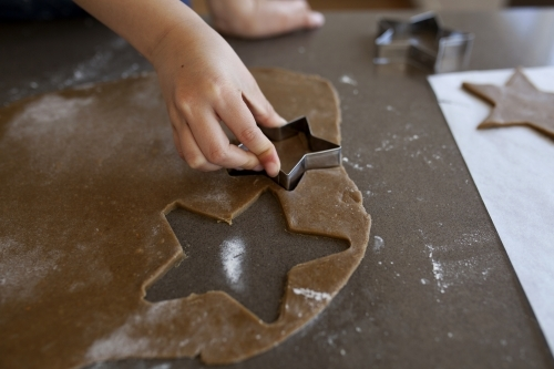 Young girl cutting shapes for gingerbread biscuits