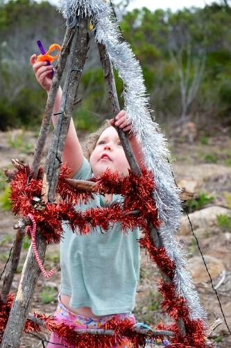 Young girl decorating Bush Christmas tree with tinsel in rural location.