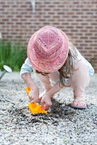 Young girl digging in wet gravel with a spade