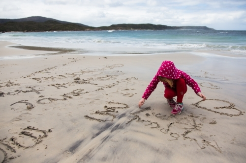 young girl drawing in the sand