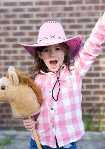 Young girl dressed as a cowgirl holding her hobby horse in the backyard yelling Yee Haw!