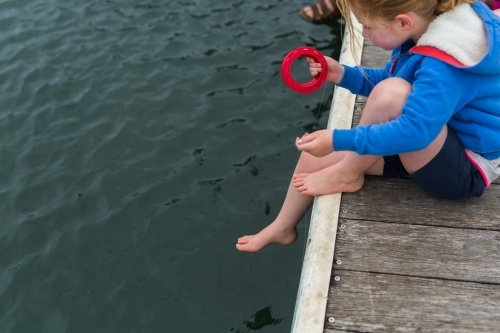 Young girl fishing off a wooden jetty with a hand reel