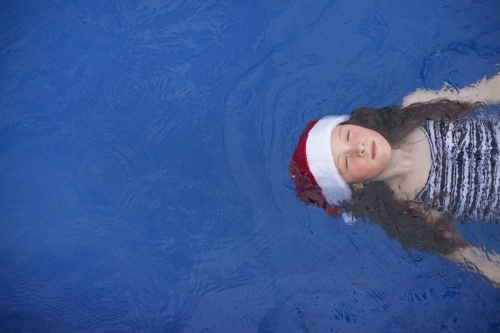 Young girl floats in a pool wearing a festive christmas santa hat