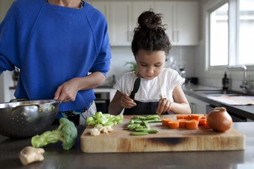 Young girl helping chop vegetables