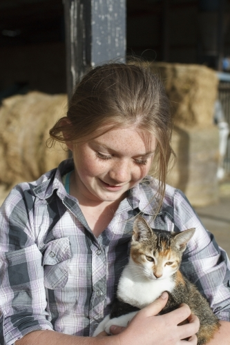 Young girl holding a farm cat