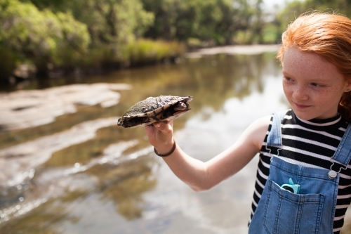 Young girl holding a turtle by the river