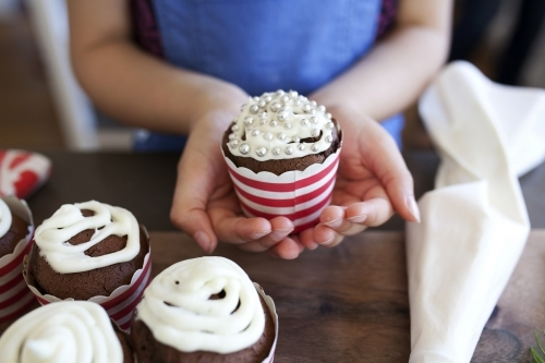 Young girl holding decorated cupcake in her hands