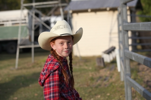 Young girl in a check shirt and cowboy hat