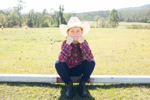 Young girl in a cowboy hat sitting on a log
