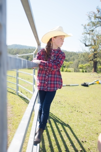 Young girl in a cowboy hat standing on a fence