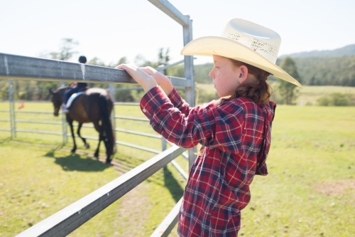 Young girl in a cowboy hat watching a horse being ridden