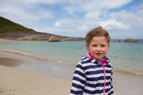 young girl in a raincoat at a beach in Spring
