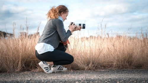 Young girl in profile kneeling taking picture of landscape