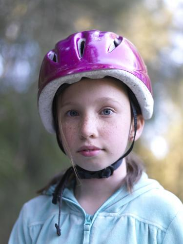 Young girl in purple helmet preparing to go bike riding