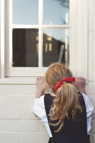 Young girl in school uniform peeking through a window