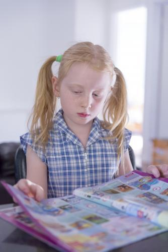 Young girl in school uniform reading a catalogue