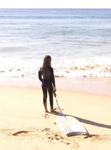 Young girl in wetsuit on beach entering water with body board
