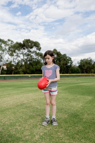 Young girl kicking an AFL ball at the park oval