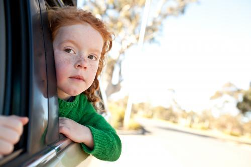 Young girl looking out of a car window