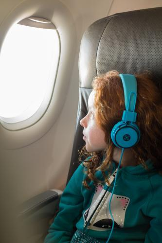 Young girl looking out of a passenger plane window
