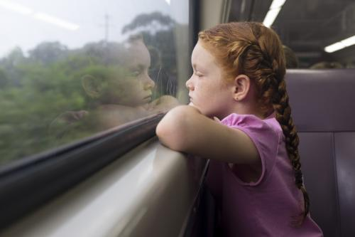 Young girl looking out the window of a train