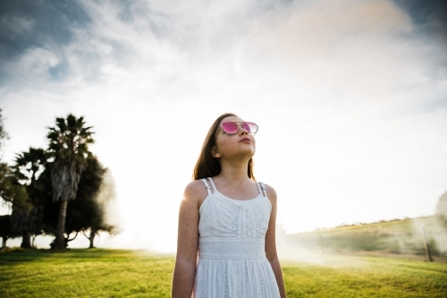 Young girl looking up at the cloudy sky