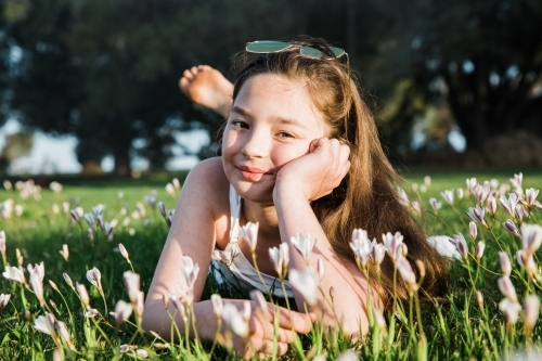 Young girl lying in a flower field smiling at camera