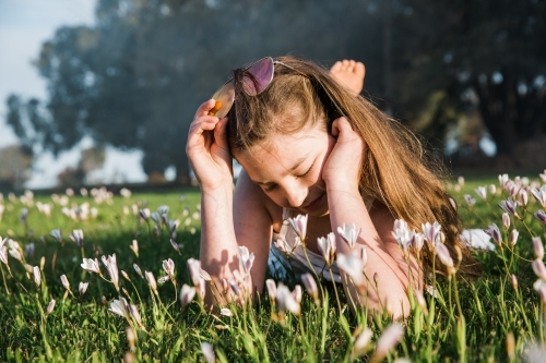 Young girl lying in grass and flowers