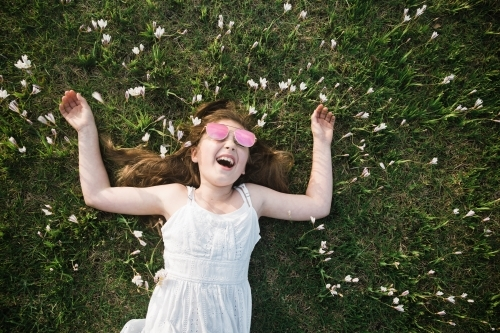 Young girl lying on the grass, laughing