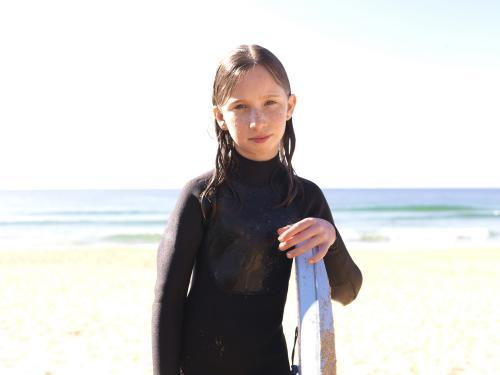 Young girl on beach in wetsuit with body board