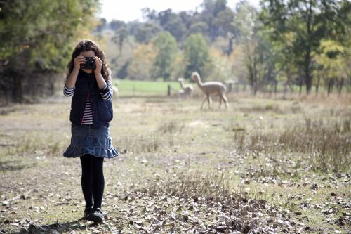 Young girl outside on a farm using a digital camera