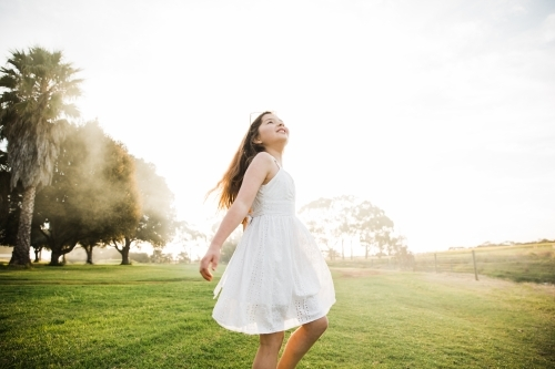 Young girl playing in a field in the sunshine